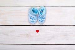 Botines azules para el muchacho y un pequeño corazón rojo en un blanco de madera Imágenes de archivo libres de regalías