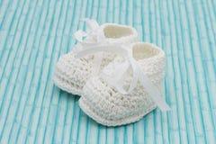 Botines blancos del bebé en el fondo de madera Imagenes de archivo