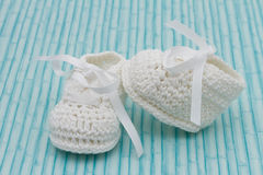Botines blancos del bebé en el fondo de madera Foto de archivo