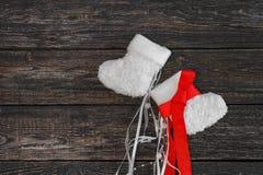 Botines calientes blancos del bebé en un fondo oscuro, Año Nuevo, la Navidad Foto de archivo