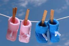 Botines del bebé rosado y azul que cuelgan en una línea de ropa Fotografía de archivo
