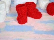 Botines hechos punto rojos del bebé, bolas rojas y blancas del hilado de lanas para hacer punto en un rosa - fondo azul foto de archivo libre de regalías