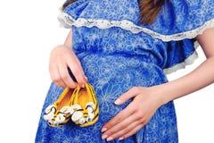 Botines hechos punto tenencia femenina de la mujer embarazada Fotografía de archivo libre de regalías