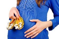 Botines hechos punto tenencia femenina de la mujer embarazada Imagenes de archivo