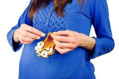 Botines hechos punto tenencia femenina de la mujer embarazada Imágenes de archivo libres de regalías