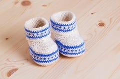 Botines lindos del bebé del ganchillo en fondo de madera Fotografía de archivo libre de regalías
