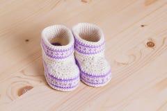 Botines lindos del bebé del ganchillo en fondo de madera Imagenes de archivo