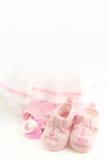 Botines rosados del bebé en un fondo rosado brillante Ropa del bebé foto de archivo