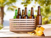 Botles de la cerveza y patatas fritas en la tabla fotos de archivo libres de regalías