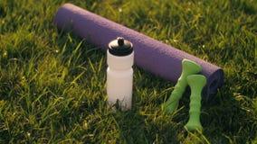 Botlle del agua, de pesas de gimnasia y de la estera de la yoga almacen de metraje de vídeo