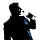 Botlle vacío de colada bebido hombre del alcohol de la silueta foto de archivo