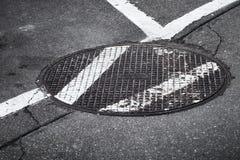 Botola rotonda della fogna sulla strada asfaltata Immagini Stock Libere da Diritti