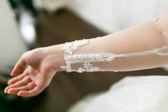 Botones blancos en la manga de encaje de un vestido de boda Imagen del primer de la mano del ` s de la novia Imagen de archivo libre de regalías