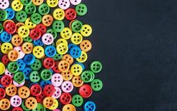 Botones brillantes coloreados mezclados en un fondo negro Foto de archivo