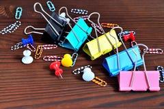 Botones, clips de papel coloreados, clips de papel en un CCB natural del marrón Imagenes de archivo