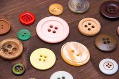 Botones coloreados de cerca en la madera Foto de archivo