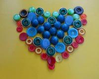 Botones coloreados en la forma de un corazón Imagen de archivo