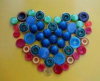 Botones coloreados en la forma de un corazón Fotos de archivo libres de regalías