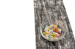Botones coloreados en la taza de cristal en el viejo tablero de madera Imagen de archivo libre de regalías