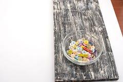 Botones coloreados en la taza de cristal en el viejo tablero de madera Imágenes de archivo libres de regalías