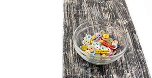 Botones coloreados en la taza de cristal en el viejo tablero de madera Foto de archivo