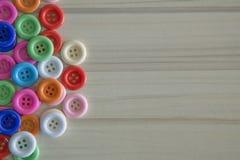 Botones coloreados multi en la tabla de madera ligera Imagen de archivo libre de regalías