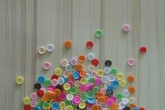 Botones coloreados multi en la tabla de madera ligera Fotos de archivo libres de regalías