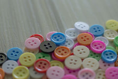 Botones coloreados multi en la tabla de madera ligera Fotografía de archivo libre de regalías