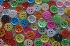Botones coloreados multi en la tabla de madera ligera Foto de archivo