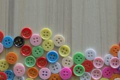Botones coloreados multi en la tabla de madera ligera Imagenes de archivo