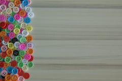 Botones coloreados multi en la tabla de madera ligera Fotografía de archivo
