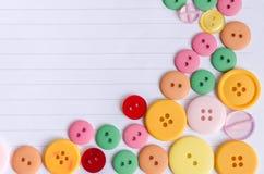 Botones coloridos del paño en el fondo de papel Fotos de archivo libres de regalías