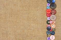 Botones coloridos viejos en la arpillera Foto de archivo