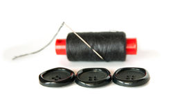 Botones con el carrete y la aguja de costura Foto de archivo