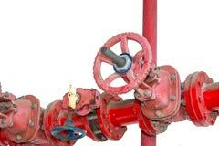 Botones de control rojos para los tubos de agua viejos del hierro en el fondo blanco Foto de archivo libre de regalías