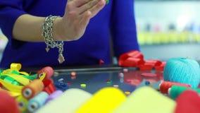 Botones de costura que caen en la tabla de cristal Tienda de costura Fuentes de costura almacen de metraje de vídeo