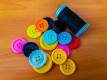 botones de diversos colores con una bobina del hilo negro Imagenes de archivo