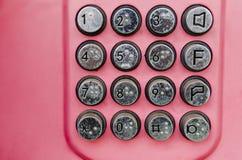 Botones del teléfono público del metal con la tabla de braille botones metálicos de un teléfono público en un fondo rojo fotografía de archivo