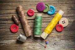 Botones e hilos de costura coloreados de la bobina en fondo de madera Imagen de archivo libre de regalías