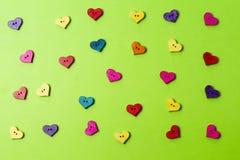 Botones en forma de corazón de madera coloridos en fondo del verdor Imagen de archivo libre de regalías