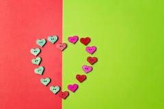 Botones en forma de corazón de madera coloridos en fondo del verdor Fotos de archivo
