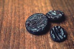 Botones negros en fondo de madera Fotografía de archivo libre de regalías