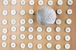 Botones y bola de costura viejos de los hilos del lino en el centro como modelo Endecha plana, visión superior Imagen de archivo libre de regalías