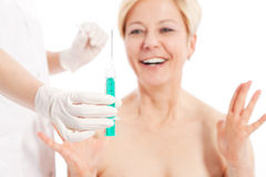 Botox - Age and beauty. Doctor is waiting with needle Royalty Free Stock Images