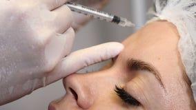 Botox e injeções do colagênio A jovem mulher obtém o procedimento da beleza com uma seringa Injeções feitas pela fêmea profission filme