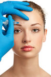 Botox injection. Cosmetic injection of botox to the pretty female face. Isolated on white background Stock Photos