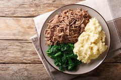 Botswana cuisine: seswaa beef stew with pap porridge and spinach. Close-up on a plate on a table. horizontal top view from above Royalty Free Stock Image