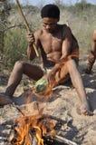 Botswana: Een naro-Buschmen die een meloen roosteren stock foto