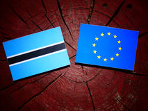 Botswana flag with EU flag on a tree stump isolated. Botswana flag with EU flag on a tree stump Stock Photo