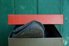 Botte noire d'orteil hors de boîte de papier colorée images stock